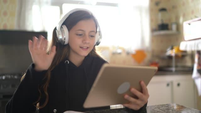 stockvideo's en b-roll-footage met meisje dat en een videovraag via tablet thuis bestudeert en maakt - online leren