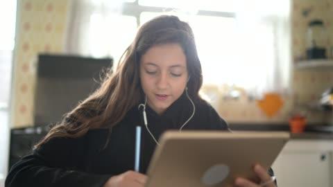 ragazza che studia e fa una videochiamata via tablet a casa - imparare video stock e b–roll