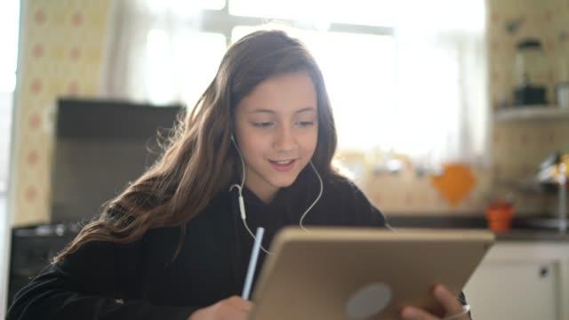 kız eğitim ve evde tablet üzerinden bir görüntülü arama yapma - okul çocukları stok videoları ve detay görüntü çekimi