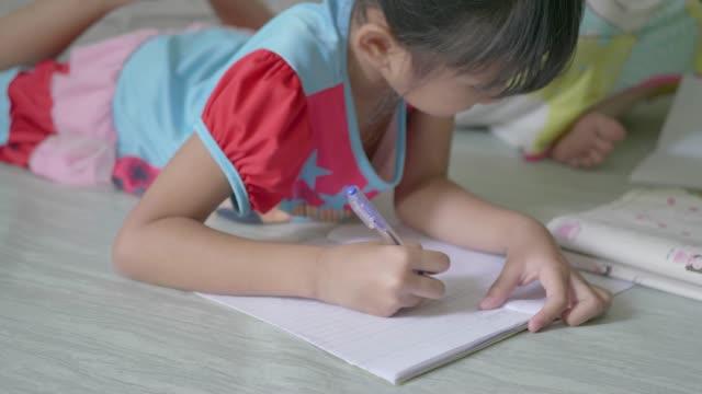 flicka som studerar lektioner hemma och skriver ner i en antecknings bok. - linjerat papper bakgrund bildbanksvideor och videomaterial från bakom kulisserna