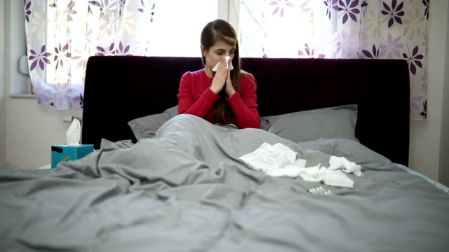 Girl suffering from a cold One woman, sitting on bed in bedroom, surrounded by pills because she is sick. double bed stock videos & royalty-free footage