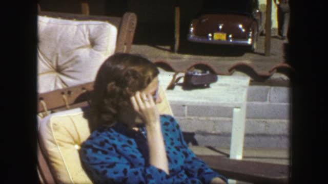 1947: Girl sun tanning in blue spotted felt dress basking in summer sunshine. video