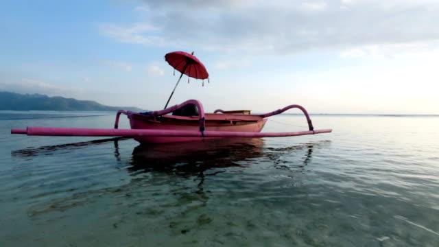 Girl sunbathing on a pink boat in Gili Trawangan Island in Bali – film