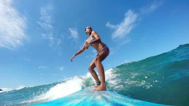 POV girl surfing riding ocean wave on sunny day Point of view shots of girl surfing in striped bikini on sunny day surf stock videos & royalty-free footage