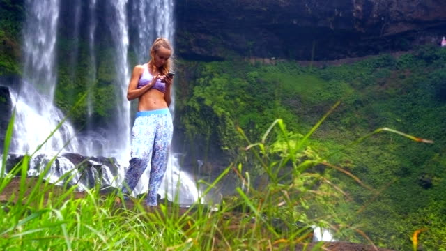 girl surfs internet on phone behind grass against waterfall