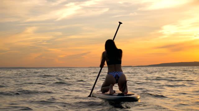 女の子は、水の上に特別なボードにサーフィン, バックビュー. - 後ろ姿点の映像素材/bロール