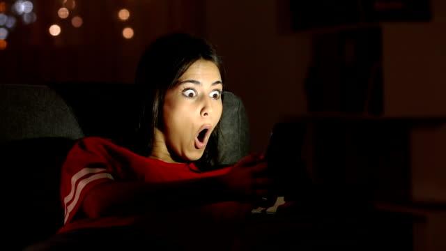 girl surprised watching phone content in the night - zwrot filmów i materiałów b-roll