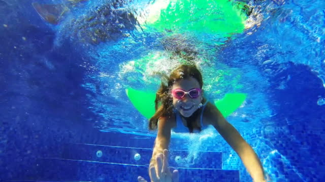 Girl swimming through a rubber ring in a swimming pool video