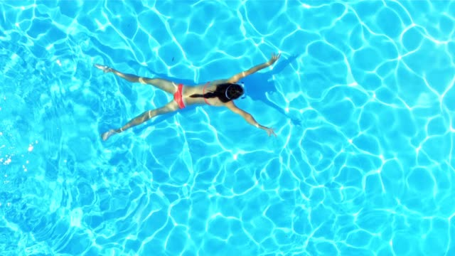 SLO MO Girl swimming underwater across a pool Slow motion medium right above shot of a girl swimming across the pool under the water. swimming stock videos & royalty-free footage