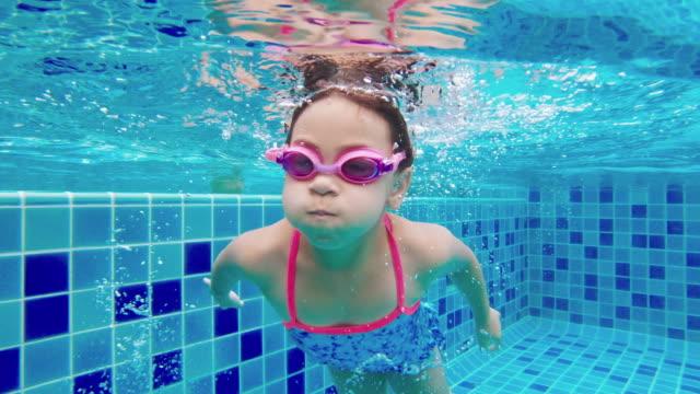 stockvideo's en b-roll-footage met meisje zwemmen onderwater en het oppakken van speelgoed uit de bodem van het zwembad - swimmingpool kids
