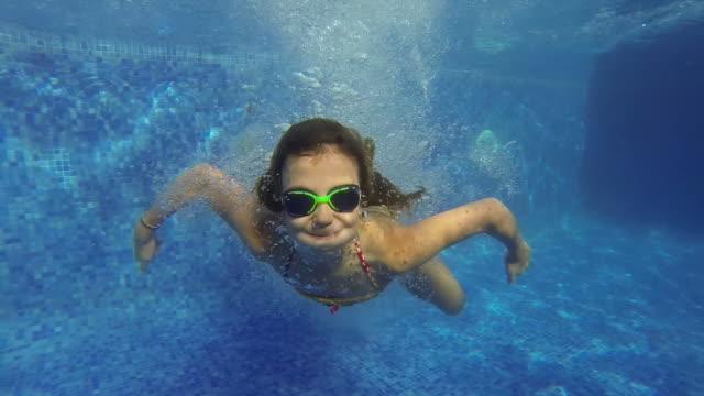 vídeos de stock, filmes e b-roll de menina nadando embaixo d'água em uma piscina - natação