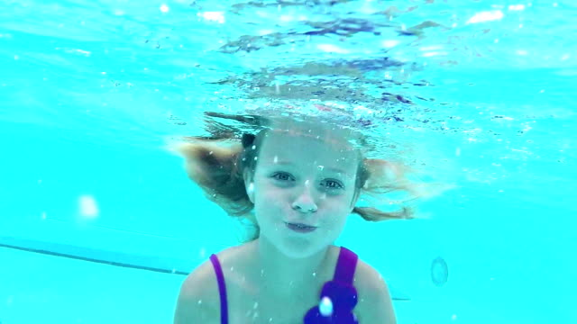 girl swimming underwater toward camera - solo una bambina femmina video stock e b–roll