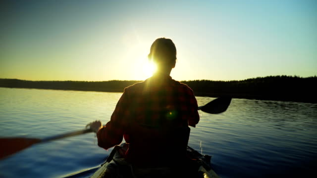 Girl swims in the kayak in the sunset