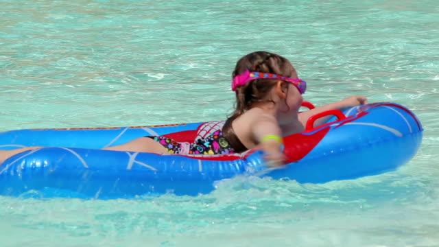 ragazza nuota nella piscina su una barca gonfiabile - brent video stock e b–roll