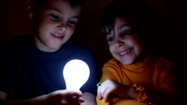 girl switchs on and off light bulb, which boy holds video