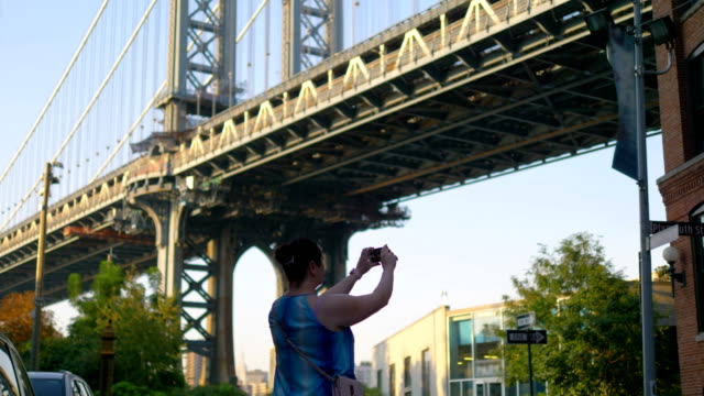 Girl Takes A Picture on Dumbo in New York City in 4K Slow motion 60fps Girl Takes A Picture on Dumbo in New York City in 4K Slow motion 60fps manhattan bridge stock videos & royalty-free footage