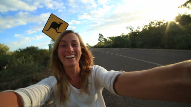 Girl takes selfie portrait with Kangaroo warning sign video