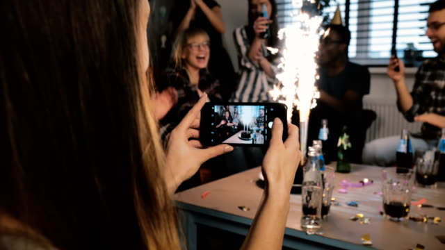 Girl taking a smartphone photo of birthday party with sparkling firework and multiethnic friends clapping slow motion video