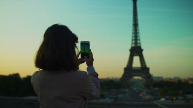 girl taking picture with smartphone of eiffel tower at sunset orange blue sky in paris during the summer. haussmanian buildings, trees, 16th, symbol, trocadero. side track pan left 4k uhd. - perfezione video stock e b–roll