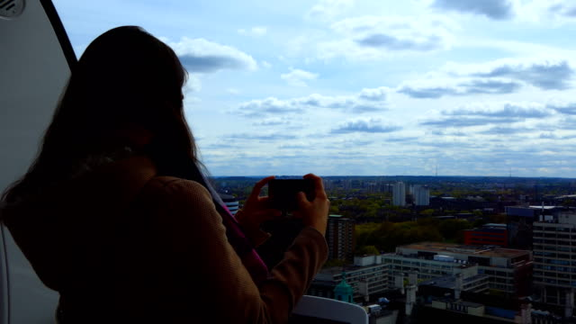 Girl taking pictures of city from above Handheld shot of girl taking cityscape pictures from   high rise building above London, England, United Kingdom.Could be any city in Europe as the view is generic general view stock videos & royalty-free footage