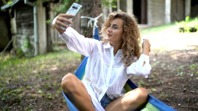 Girl taking selfie in hammock video