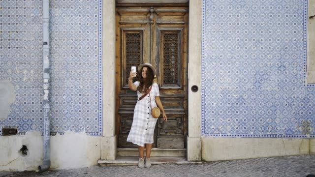 vídeos de stock e filmes b-roll de girl taking selfie near door and wall with abstract pattern - people lisbon