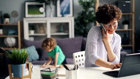 stockvideo's en b-roll-footage met meisje praten op mobiele telefoon werken met laptop, terwijl haar zoon spelen thuis - huiselijk leven