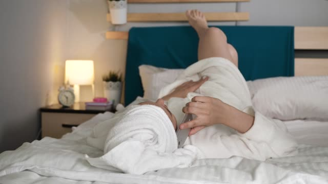 Girl talking on phone. Woman in bedroom with towel on her head and in white bathrobe lies on back and talks on her cell phone. Medium shot Girl talking on phone. Woman in bedroom with towel on her head and in white bathrobe lies on her back and talks on her cell phone. Medium shot view wearing a towel stock videos & royalty-free footage