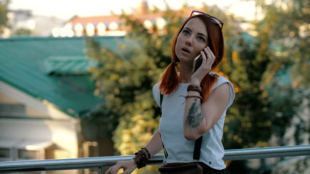 girl talking on smart phone on background modern city. woman calling by mobile - ragazza auricolari rossi video stock e b–roll