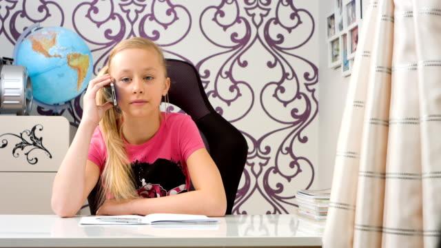 girl talking on smartphone and doing homework - çalışma kitabı stok videoları ve detay görüntü çekimi