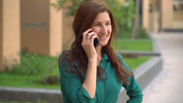 stockvideo's en b-roll-footage met meisje dat op de telefoon buiten spreekt - s
