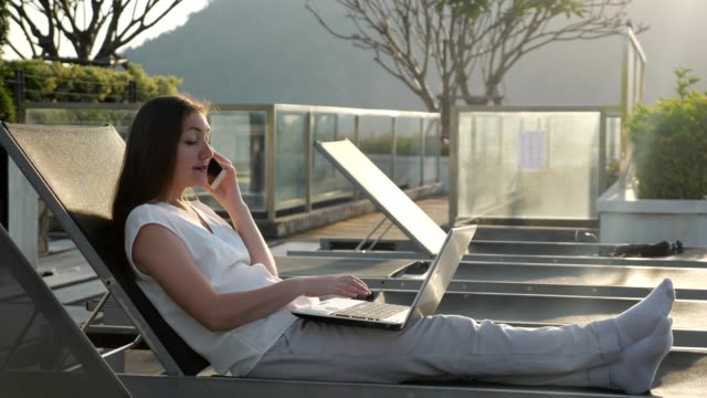 girl talks on phone typing on laptop at hotel rest lounge