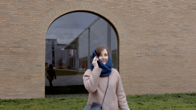 Girl talks on the phone in front of big window video
