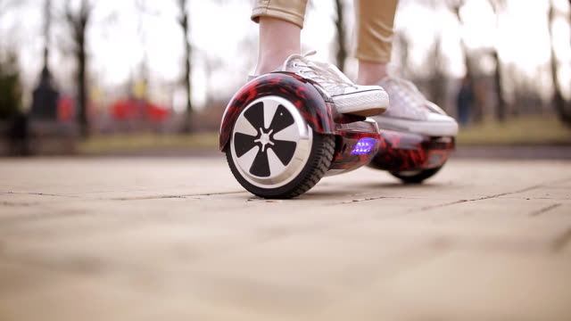 girl teenager spinning on smart scooter. close-up of feet on a electronic scooter. - spiedino video stock e b–roll
