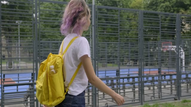 girl teenager, student of 15 years walking with yellow backpack in white t-shirt near street basketball court. - maglietta bianca video stock e b–roll