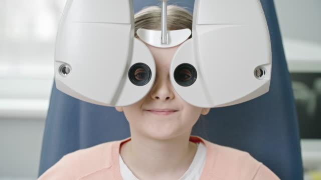 vidéos et rushes de fille testant sa vision avec le phoropter numérique - réfracteur