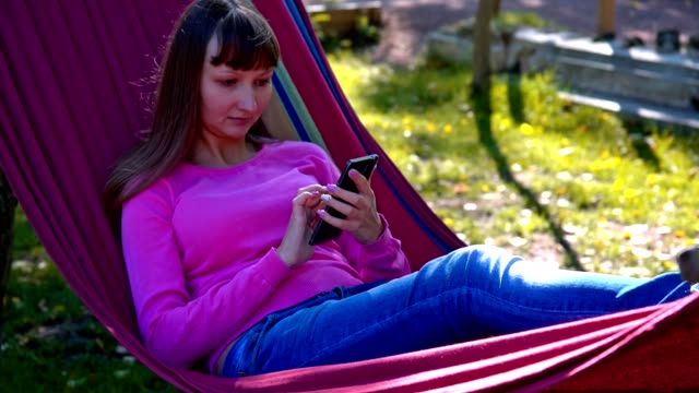 Girl texting on mobile phone on hammock video
