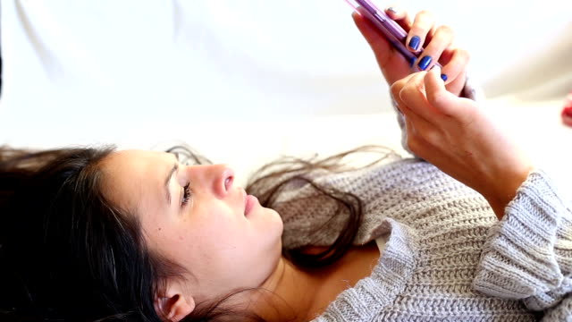 Girl texting on smartphone at home video