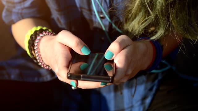 stockvideo's en b-roll-footage met meisje texting op smartphone buiten - tienermeisjes