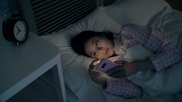 ベッドの上の少女のテキスト メッセージ。 - スマホ ベッド点の映像素材/bロール