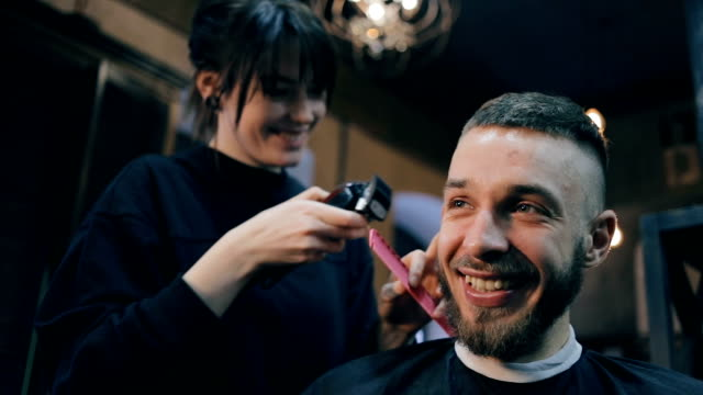 Girl the hairdresser shears the guy with a clipper. video