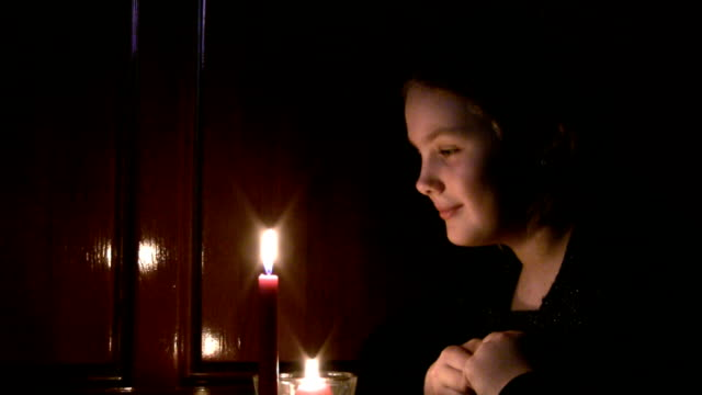 girl the teenager looks at a burning candle. - endast en tonårsflicka bildbanksvideor och videomaterial från bakom kulisserna