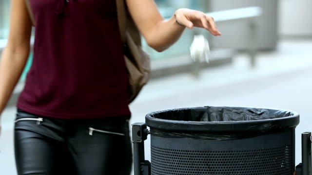 girl throwing a paper into bin - city walking background video stock e b–roll