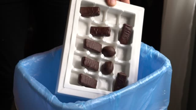 Girl throwing chocolate sweets into household plastic trash bin Girl throwing chocolate sweets into household plastic trash bin. Environmental Impact of Food Waste. Healthy eating leftovers stock videos & royalty-free footage