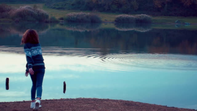 girl throwing rocks in the lake. Shot in slow motion video