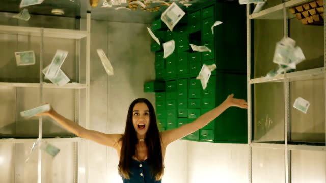 Girl throws lot of dollars over her head in slow motion and rejoices from wealth