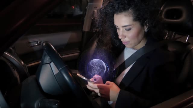 Girl touches holographic navigation touch screen of mobile phone while sitting behind steering wheel