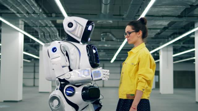 ein mädchen berührt die hand des weißen cyborg, schaut es sich an. - fortschritt stock-videos und b-roll-filmmaterial