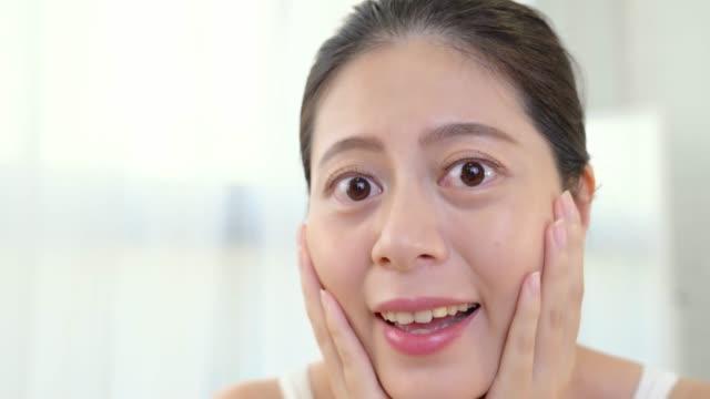 鏡の前に彼女の顔に触れる女の子 - スキンケア点の映像素材/bロール