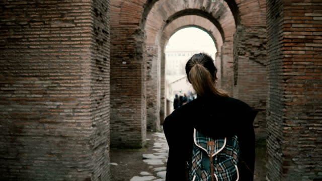 Girl tourist is walking in historical centre of Rome, Italy. Woman passing the chain of ancient arcs made of red brick video